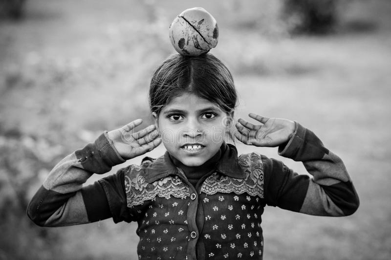 A black and white image with an indian girl with a fruit on her head royalty free stock photos