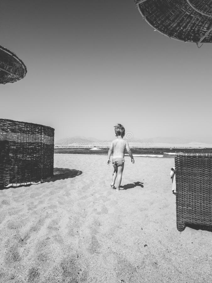 Black and white image of little toddler boy walking on the sea beach between sun beds and umbrellas. Child relaxing and stock photos