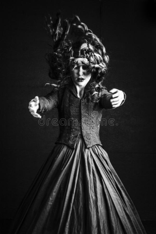 Black and white image of long-haired, brunette Victorian woman in a black ensemble. Long-haired Victorian woman in a black ensemble. This image had a Gothic feel royalty free stock photography