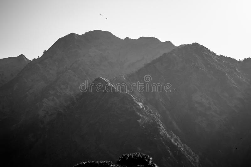 Black and white image of a mist covered mountain illuminated by sunlight with birds flying over. Winter concept stock photo