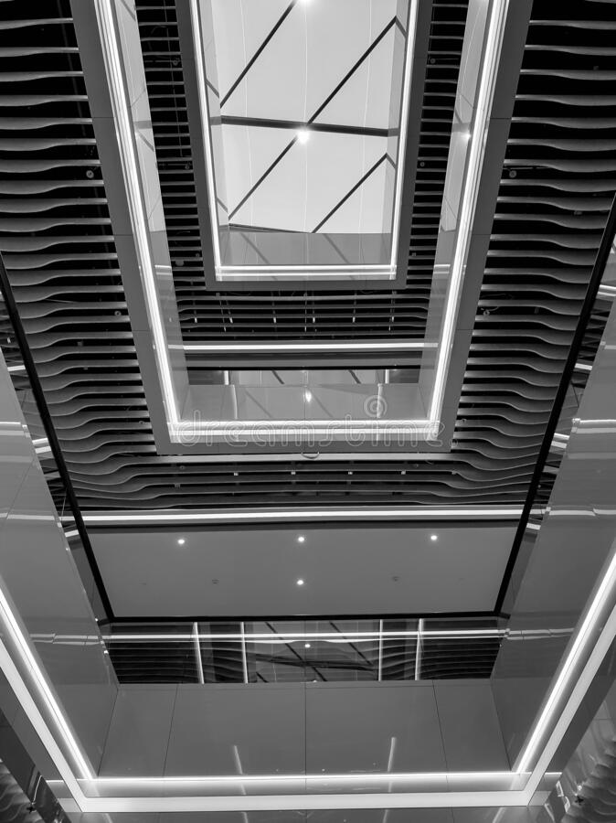 Black and white image of modern interior of long halls and balconies at office building royalty free stock photography