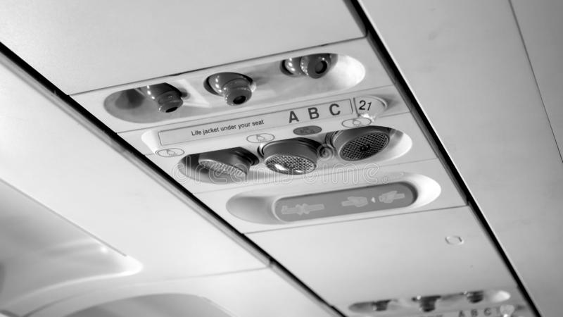 Black and white image of passenger control panel on the ceiling of jet airplane stock photos