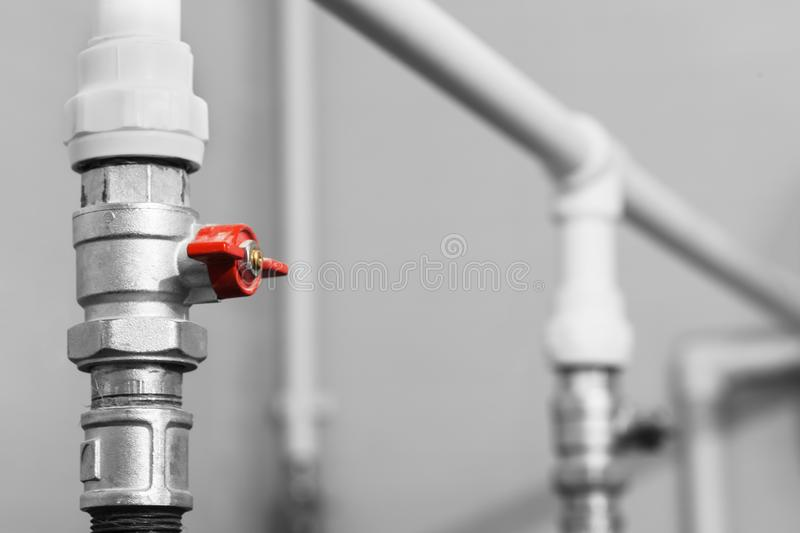 Black and white image of plumbing valve with red faucet on the plastic water pipe of plumbing system. Close-up royalty free stock photo