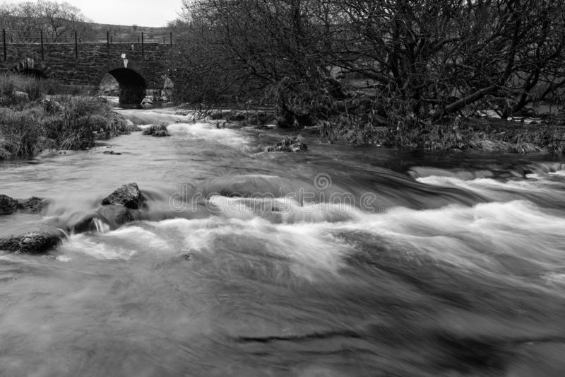 Black and white image of the River Lyd running under the B3357 on Dartmoor stock image