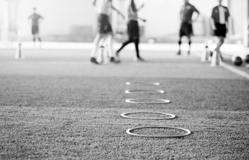 Black and white image of selective focus to ring ladder marker and cone are soccer training equipment stock photography