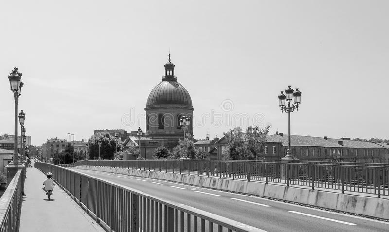 Black and white image of small child safely riding a bicycle alone on a scenic European bridge. Black and white B&W of small child riding safely on a bicycle stock images