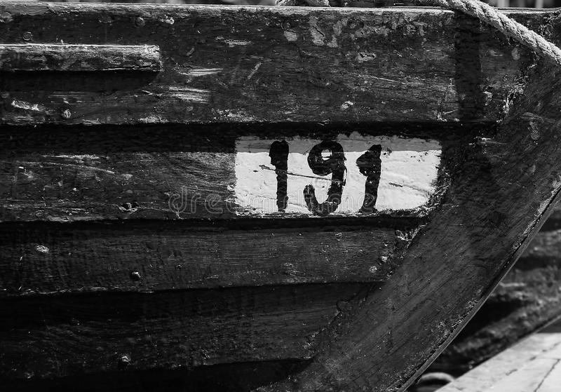Black and white image of stern of a docked wooden boat royalty free stock photos