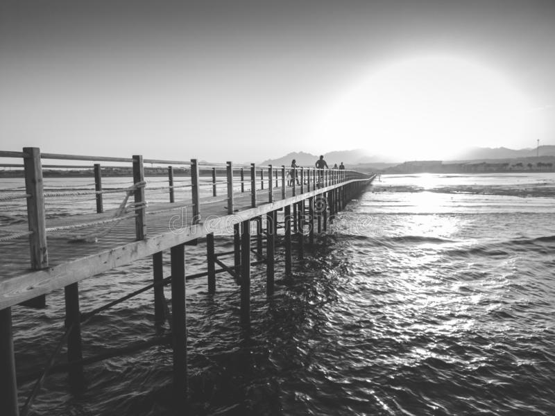 Black and white image of sun setting down over the ocean waves and long wooden pier. Black and white photo of sun setting down over the ocean waves and long stock photo