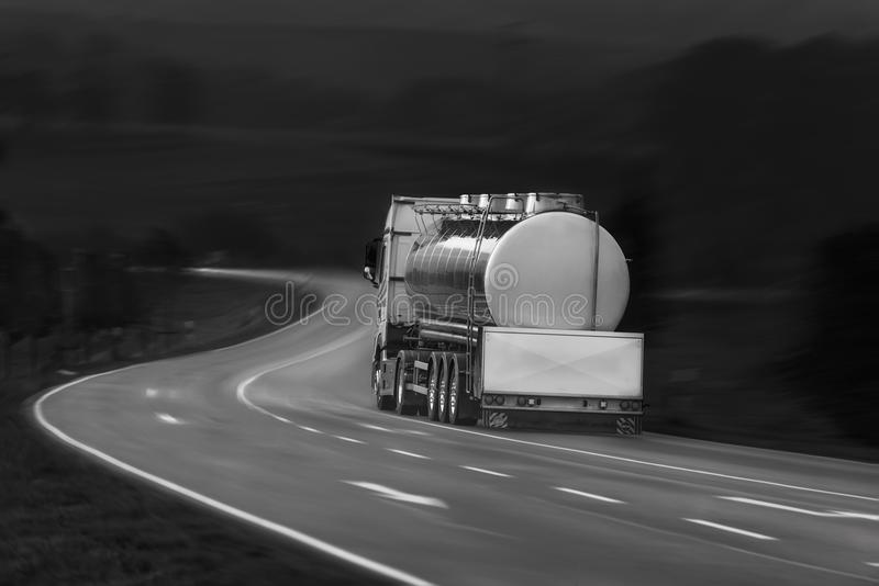 Tanker truck in motion. Black and white image with tanker truck driving on a countrye road, oute the german city Schwabisch Hall, Baden Wurttemberg, Germany stock image