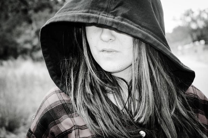 Black and white image of teenager wearing a hoodie stock photo