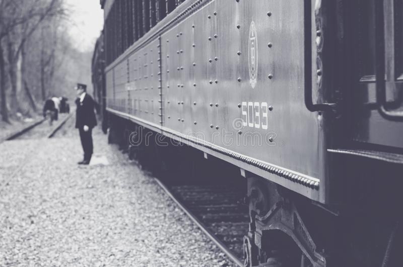 Black and White Train with Conductor Standing Nearby stock image