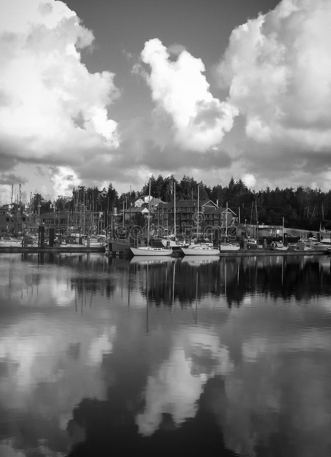 Black and white image of Ucluelet harbour view with big puffy clouds reflected in the water. stock images