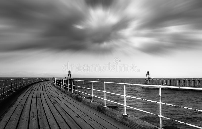 Black and white image of Whitby pier royalty free stock photography