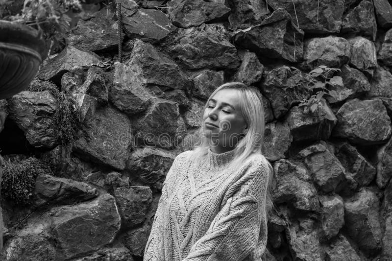 Black-white image of a young blonde girl in a gray knitted sweater on a background of a stone wall in the fall. Fashionable stock photo
