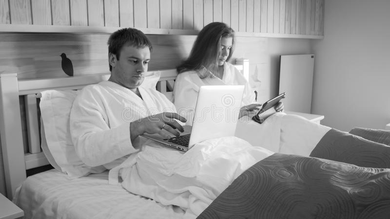 Black and white image of young couple of businessman and businesswoman working in bed at morning. Black and white photo of young couple of businessman and royalty free stock photography
