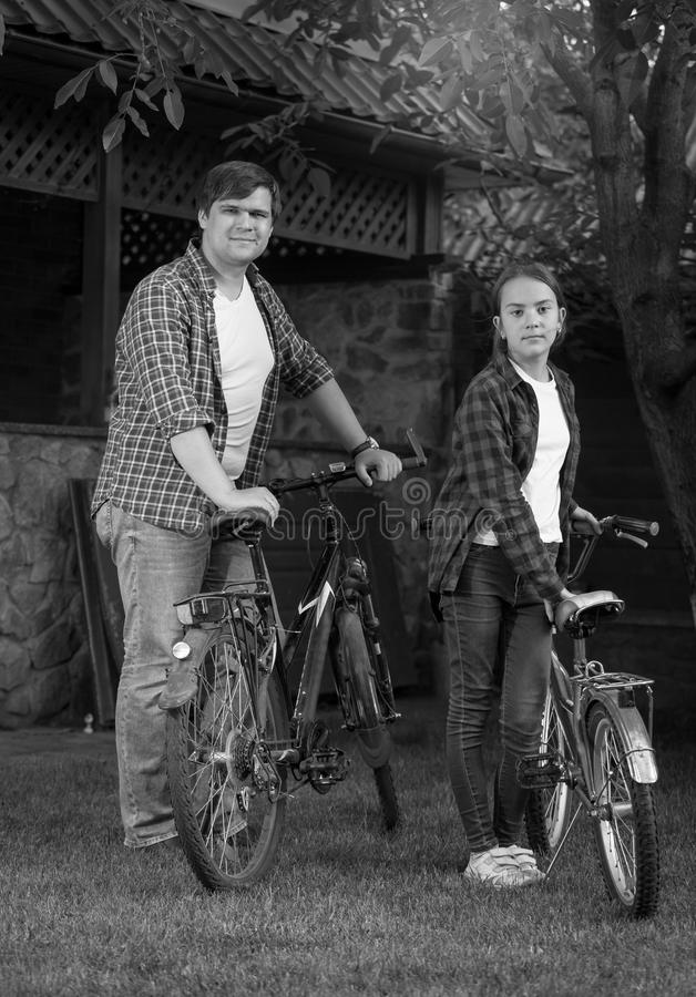 Black and white photo of young man with teenage daughter posing with bicycles at house backyard stock photos