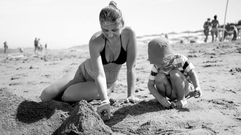 Black and white photo of young mother with her 3 years old child son sitting on the sandy sea beach, playing with toys royalty free stock images