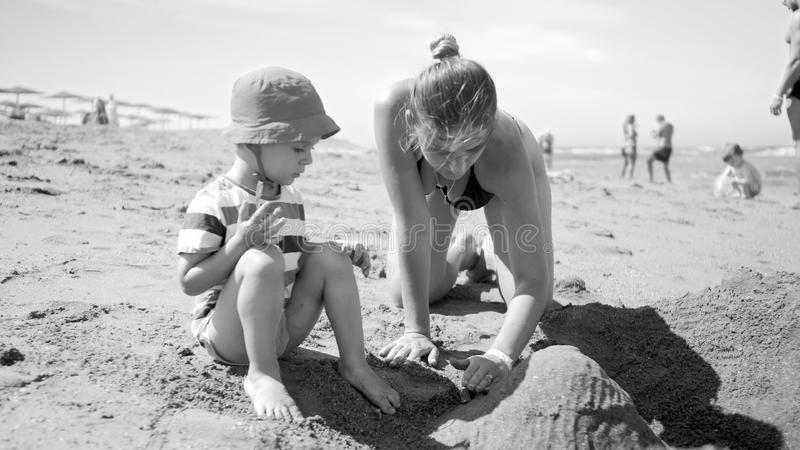Black and white photo of young mother with her 3 years old child son sitting on the sandy sea beach, playing with toys stock image