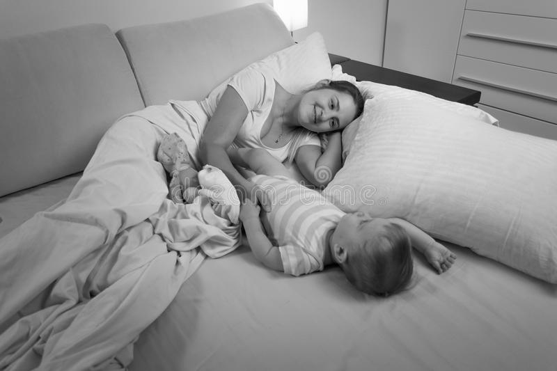 Black and white image of young mother sleeping with her baby boy. Black and white photo of young mother sleeping with her baby boy in bed royalty free stock photo