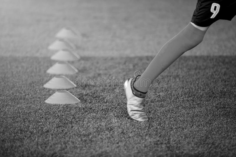 Black and white of kid soccer players Jogging and jump between cone marker stock photography