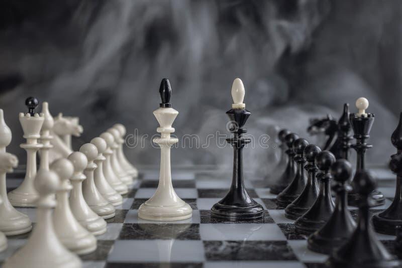 Black and White Kings of chess setup on dark background stock photo