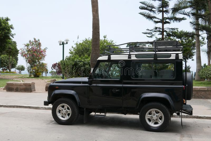 Black and white Land Rover Defender in Lima. Lima, Peru. December 27, 2017. Side view of a mint condition black Land Rover Defender with white top. The car is royalty free stock photography