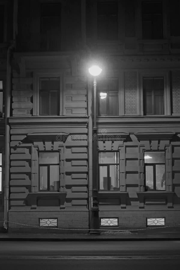 Black and white Lantern burning at the house in the evening. Black and white lantern on the street near the house in the evening royalty free stock photo