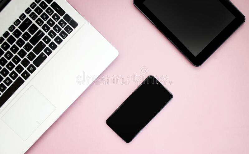 Black-white laptop keyboard, black tablet, black mobile phone on a pink background. Copy space. Top view. Computer work. Flat lay royalty free stock photos