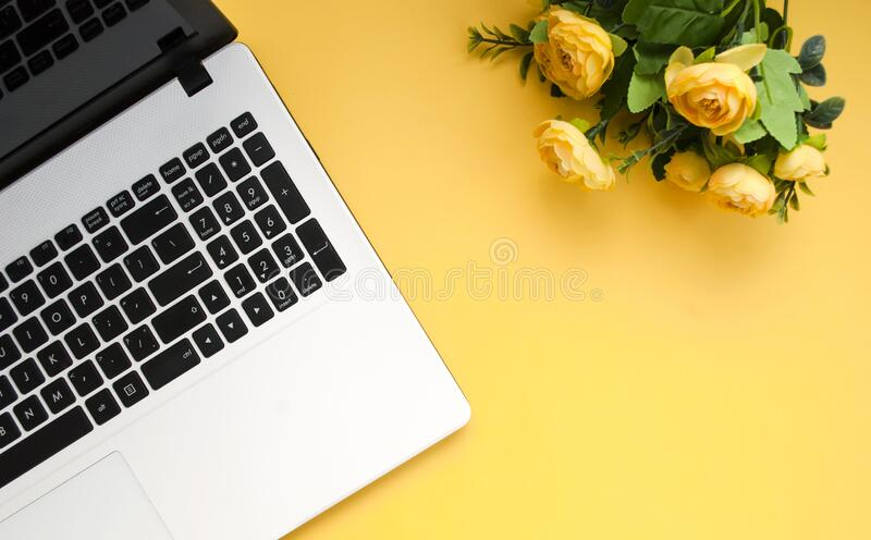 Black-white laptop keyboard, yellow flowers on an orange background. Flat lay. Top view. Copy space stock images