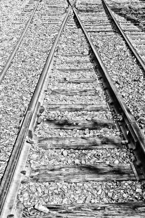 Railroad tracks junction B&w. Black and white leading lines of two railroad tracks meeting at a junction stock photo