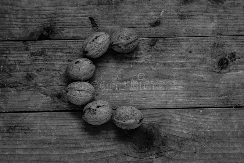 Black and white Letter C from walnuts. Black and white of top view of english alphabet made from walnuts on a wooden table. Letter C stock photo