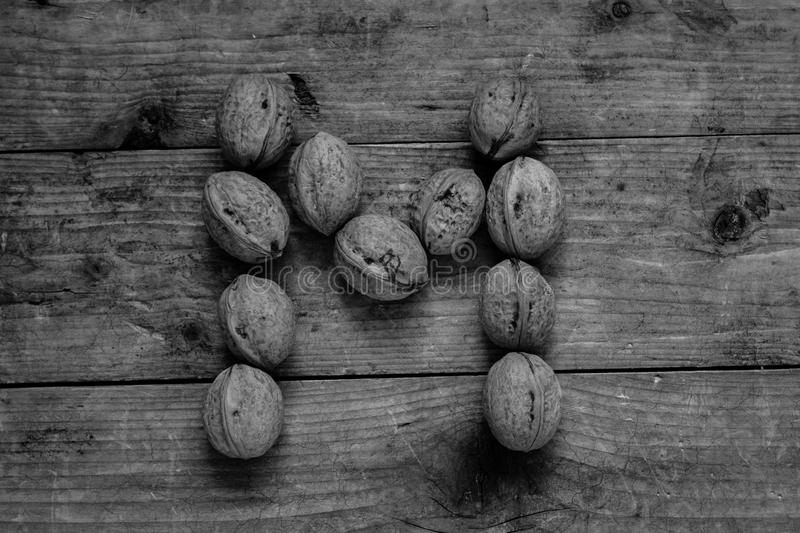 Black and white Letter M from walnuts. Black and white of top view of english alphabet made from walnuts on a wooden table. Letter M royalty free stock photography