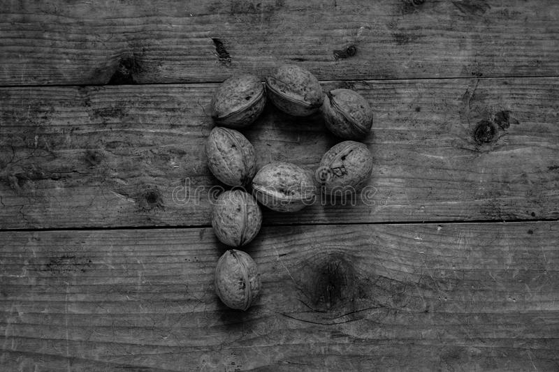 Black and white Letter P from walnuts. Black and white of top view of english alphabet made from walnuts on a wooden table. Letter P royalty free stock photos