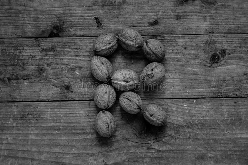 Black and white Letter R from walnuts. Black and white of top view of english alphabet made from walnuts on a wooden table. Letter R royalty free stock photos