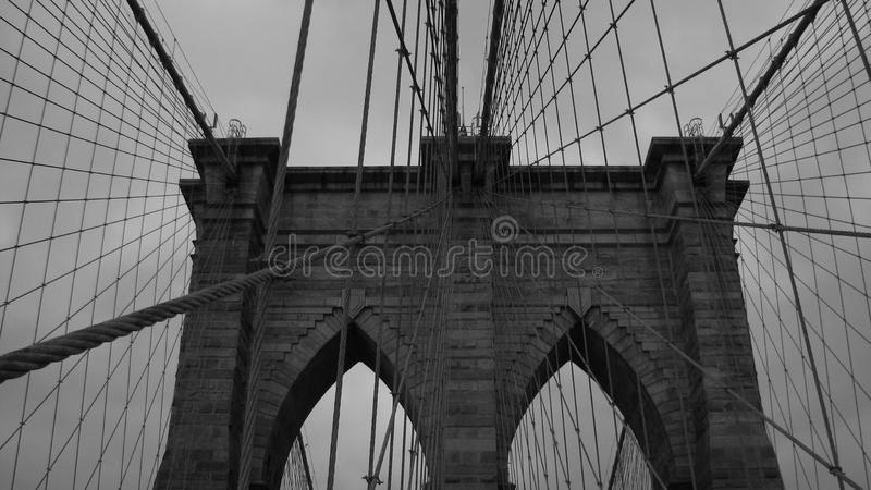 A black and white look at the cables of the Brooklyn Bridge looking onto Manhattan - USA stock photo