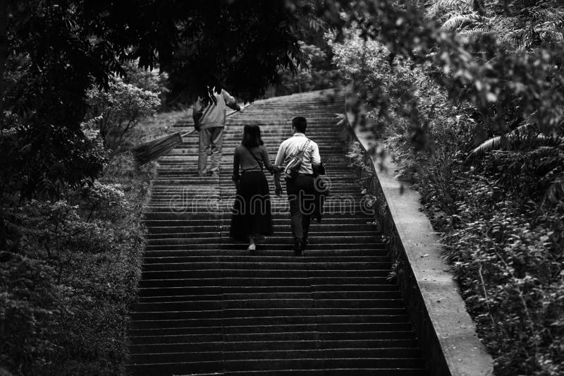 Black and white Lover hand in hand walking on the stone ladder royalty free stock images