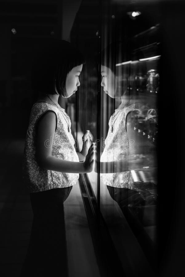 The black and white low key image of the young girl staring at the showcase, which is like a mirror, reflecting her as another. stock photos