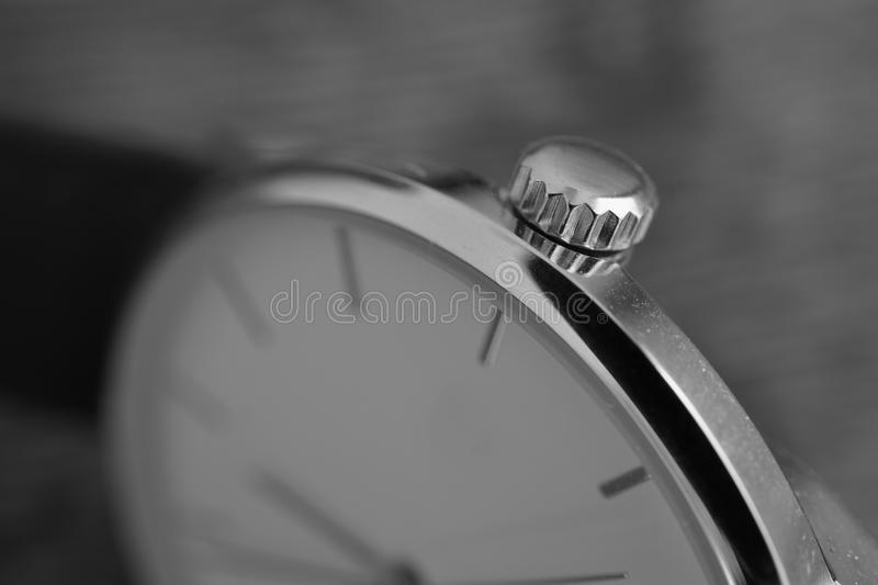 Black and white macro detail of a golden indented crown set in the gold-plated watch as a symbol of luxurious timepiece stock image
