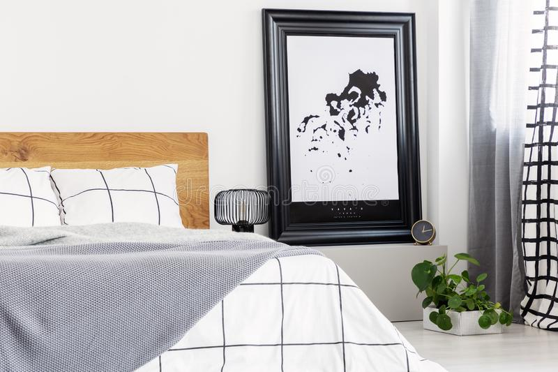 Black and white map in black frame in trendy bedroom interior with chequered bedroom royalty free stock image