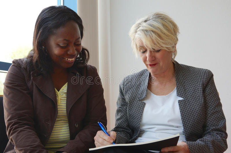 Black and white mature women working together royalty free stock image