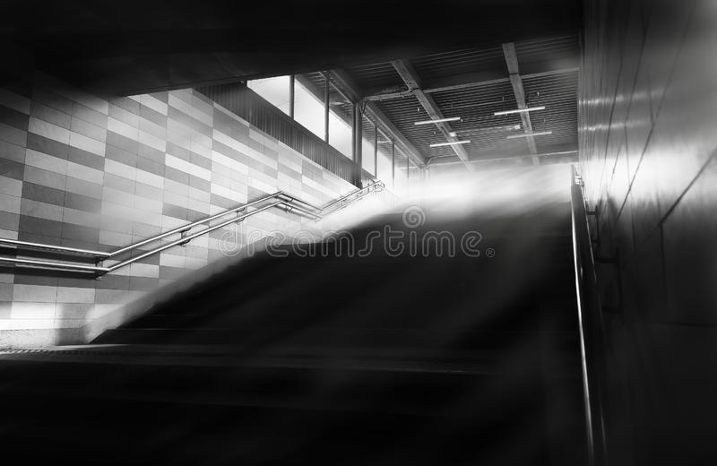 Black and white metro upstairs with light rays background stock photo