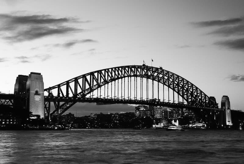 Black and white mighty steel Sydney Harbor bridge crossing the ocean royalty free stock photo