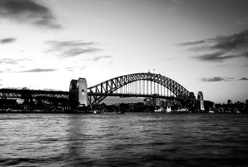 Black and white, mighty steel Sydney Harbor bridge crossing the ocean stock image