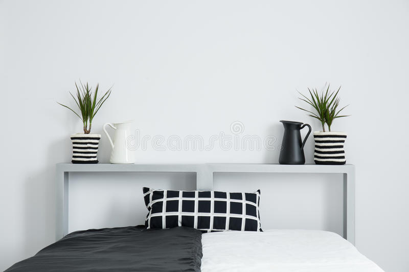 Plants stand symetrically on bolster. Black and white milk jug and plants stand symetrically on bolster of king-size bed with checkered pillow royalty free stock photo