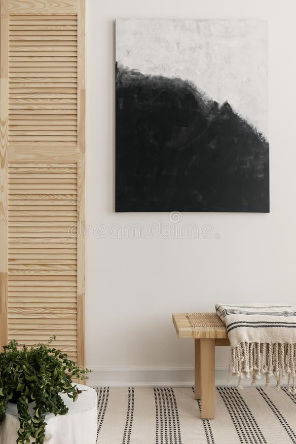 Black and white modern painting on the wall of elegant waiting room with wooden bench with striped blanket and green plant in the. Corner royalty free stock image
