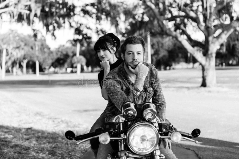 Portrait of Attractive Good Looking Young Modern Trendy Fashionable Guy Girl Couple Riding on Green Motorcycle Cruiser Old School royalty free stock photo