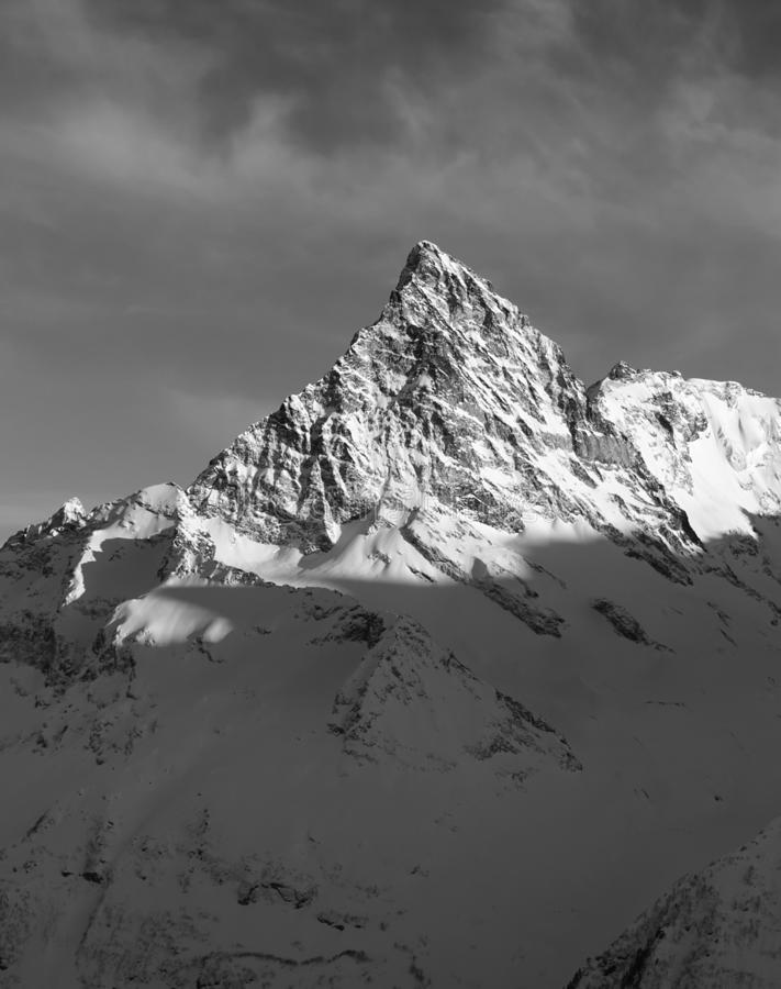 Black and white mountain peak in snow at winter sunset. Caucasus Mountains, region Dombay, Mount Belalakaya royalty free stock image