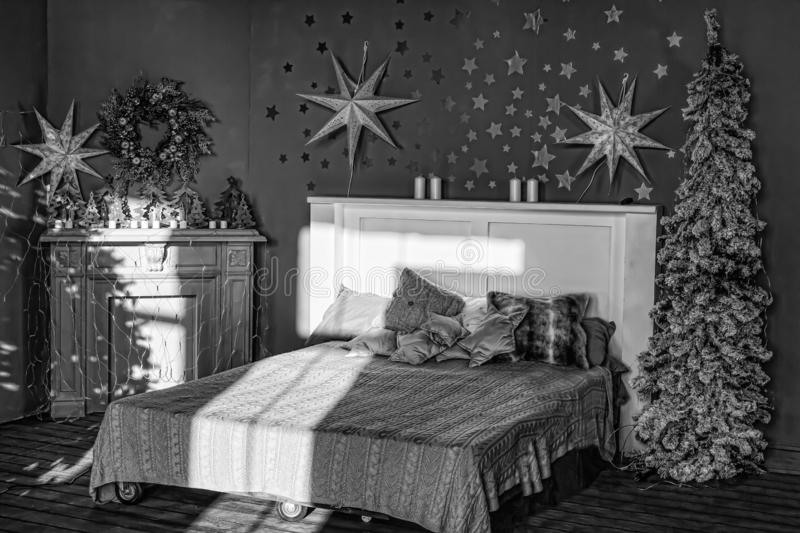 Black and white, New Year`s interior. Bedroom with fireplace decorated with Christmas stars. stock photography