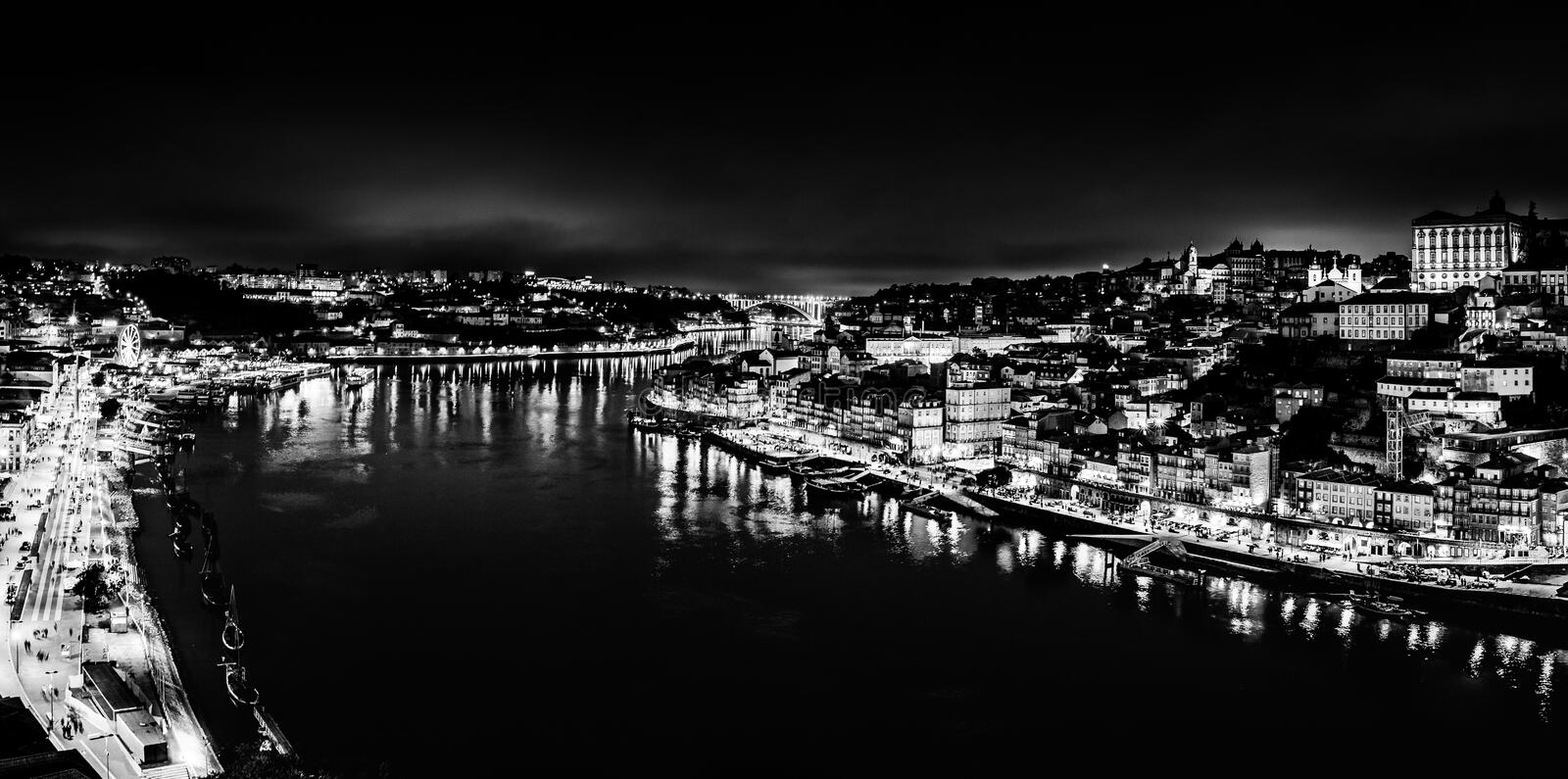 Black and white night cityscape panorama of Porto old town and river Douro banks skyline with water reflections in Porto, Portugal. Porto, Portugal: Black and royalty free stock photography