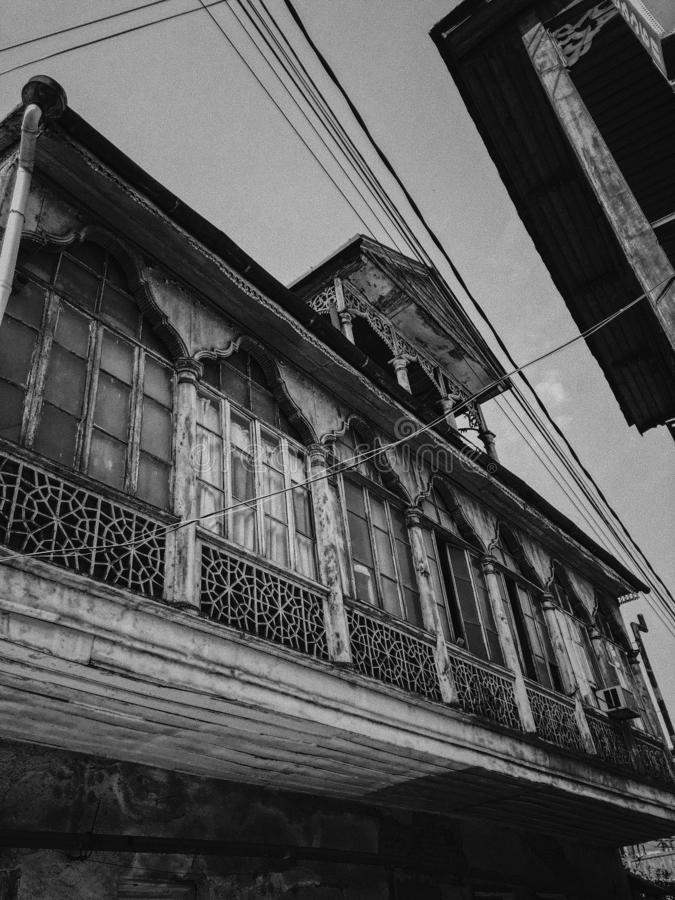 Black and white old antique balcony of a wooden european house. European old architecture. Vertical photo.  stock photography